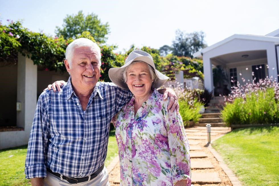 Older Couple smiling, standing in front of house