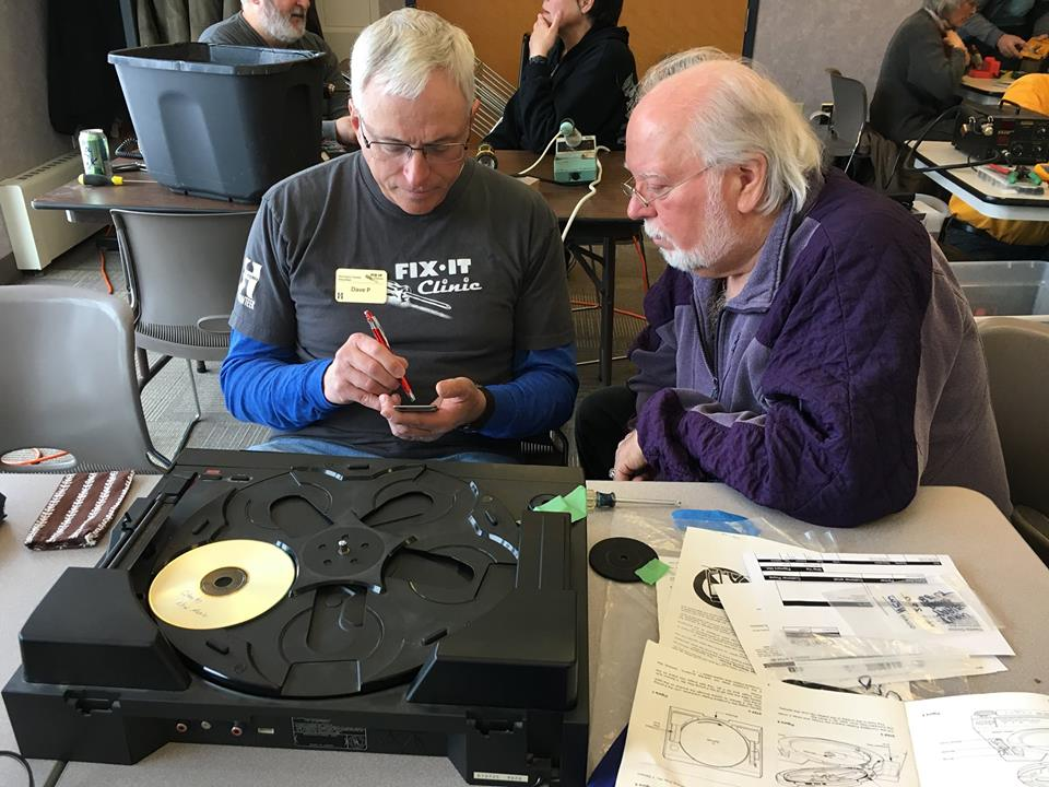 Man fixing a CD player while another looks on